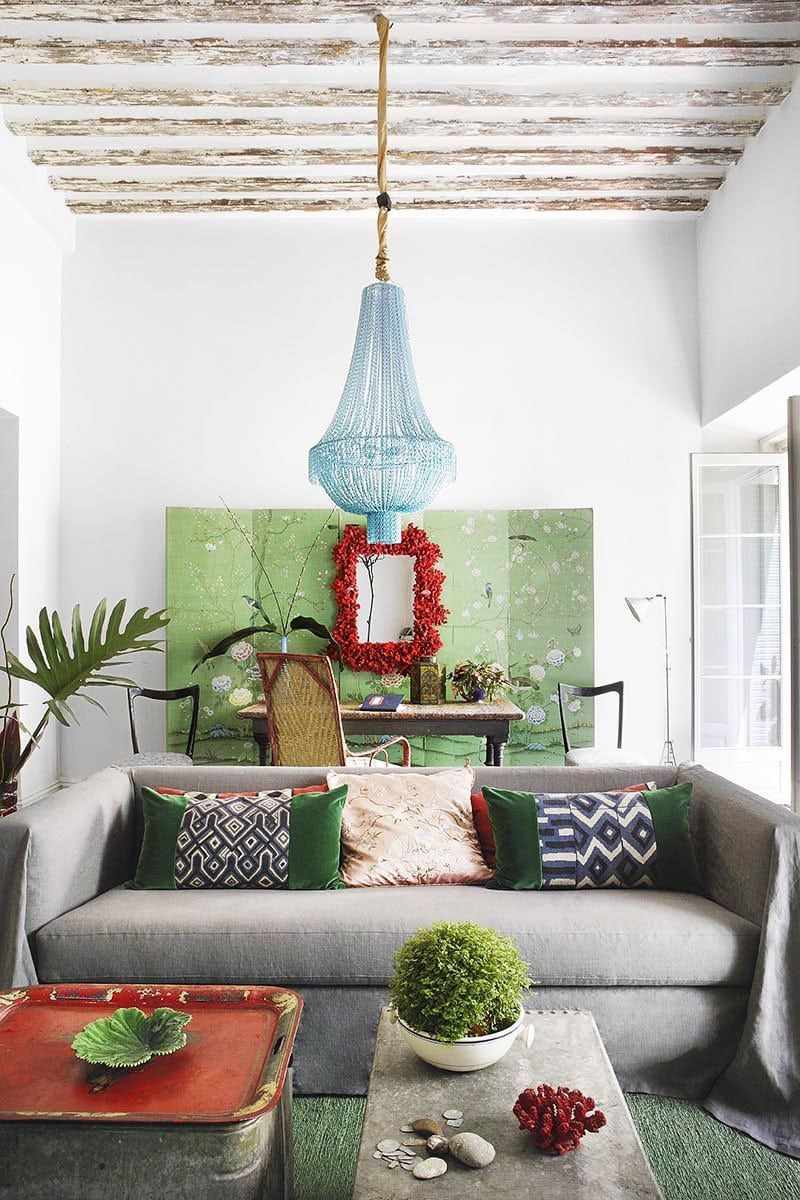 A lush and laid-back green living room, with mounted chinoiserie screen and blue beaded chandelier.