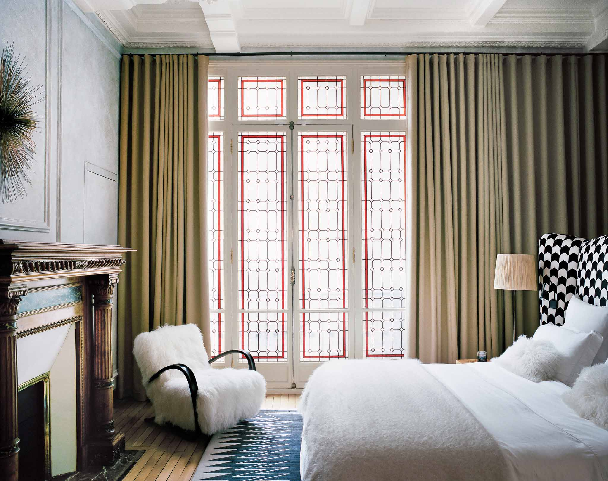 A modern bedroom by Studio KO with original stained-glass windows and graphic patterns on @thouswellblog
