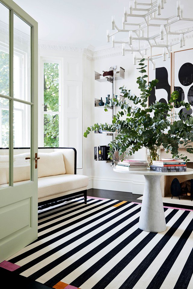 A modern London townhouse with green interior doors and striped rug on @thouswellblog