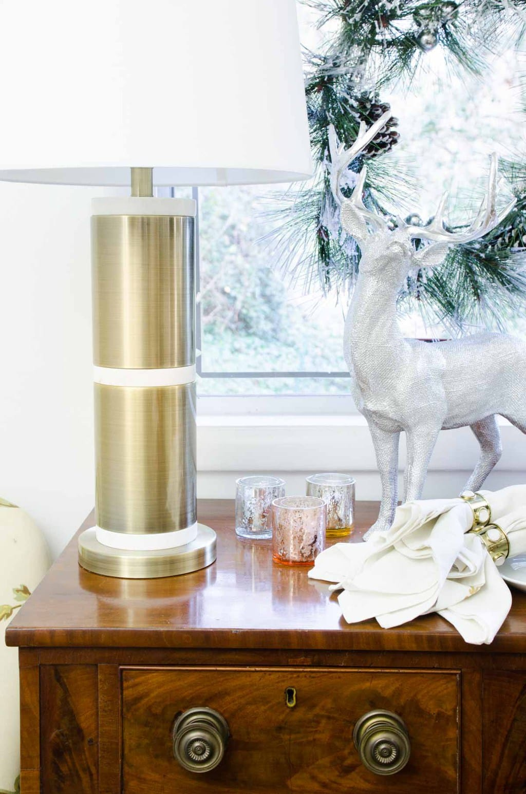 Buffet with holiday decor, brass lamp and silver reindeer