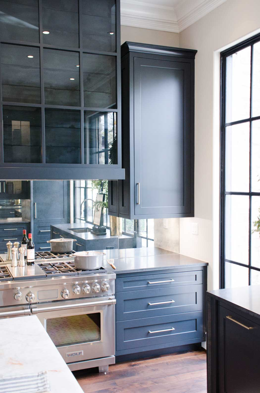 Blue slate kitchen cabinets with mirrored backsplash