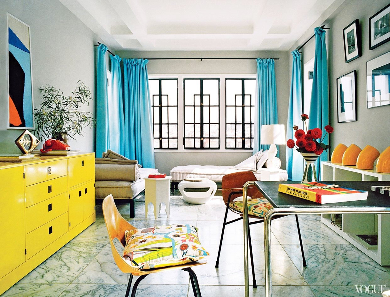 A colorful Moroccan living room with blue curtains and yellow dresser