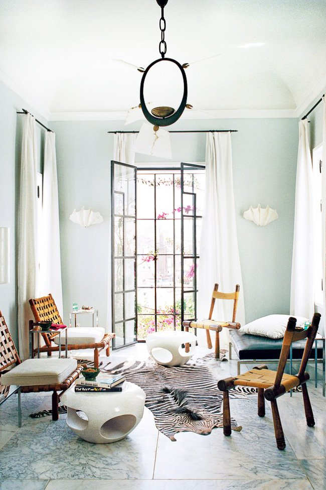 A light-filled living room with pale blue walls and marble floors on @thouswellblog
