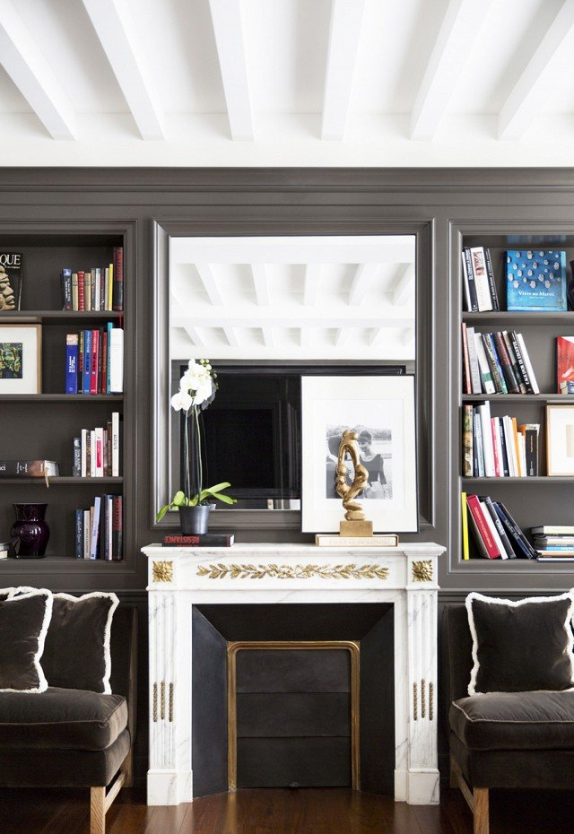 Charcoal living room walls with built-in bookshelves and mirror above marble fireplace via @thouswellblog