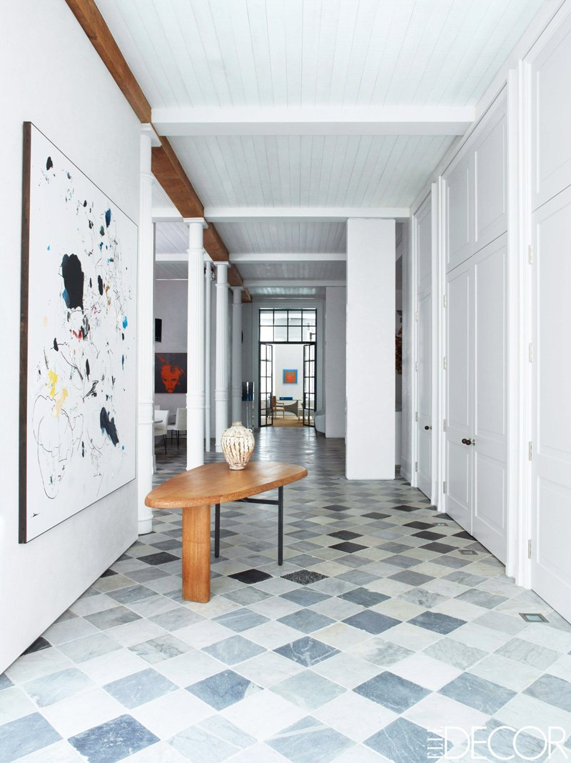 The Elegant Entry Of A Manhattan Loft With Marble Tiles And Modern Art Via