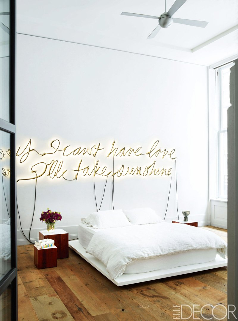 Neon sign above a simple platform bed in a loft bedroom via @thouswellblog