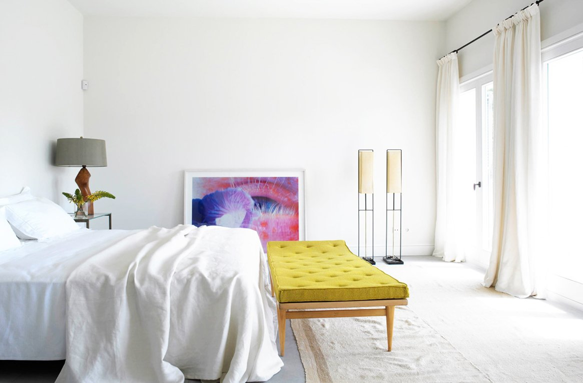 Simple white bedroom with modern art and yellow bench on @thouswellblog