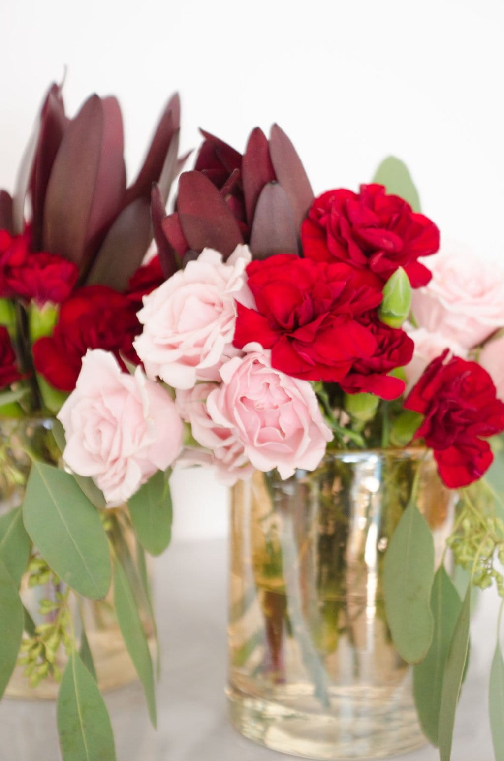 Pink roses, red carnations, leucadendron, and seeded eucalyptus via @thouswellblog