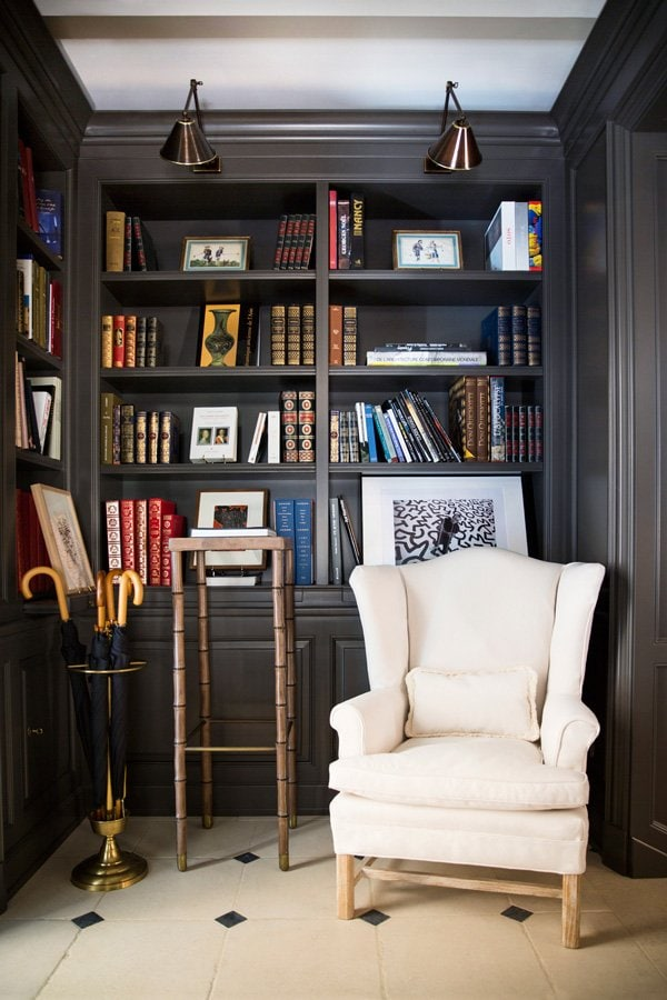 Armchair with black built-in bookshelves in a French hotel via @thouswellblog