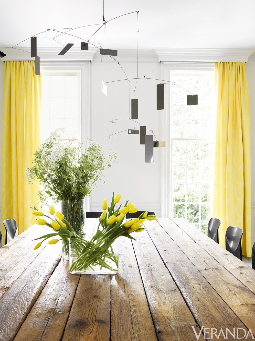 Dining room with yellow curtains and modern mobiles via @thouswellblog