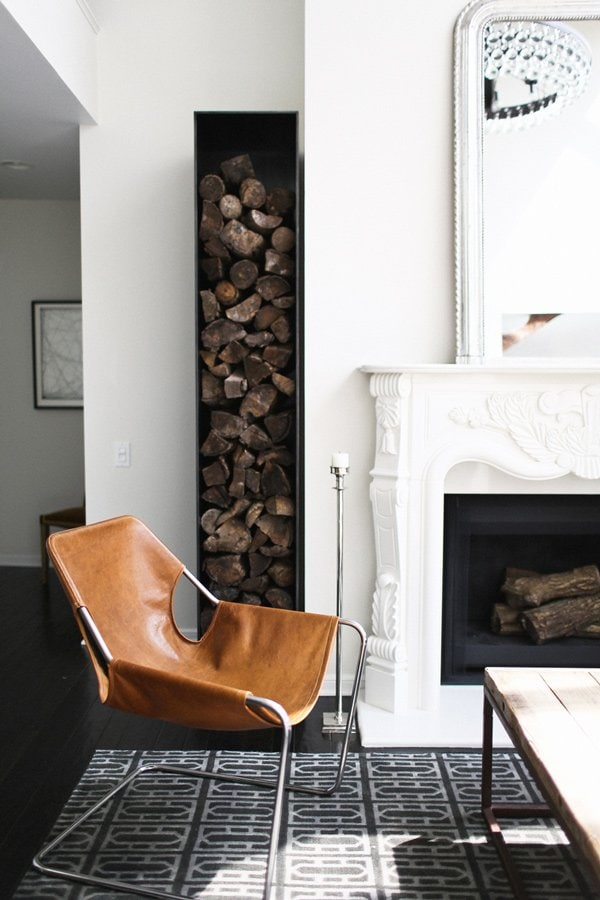 Modern fireplace, stacked wood and leather chair via @thouswellblog