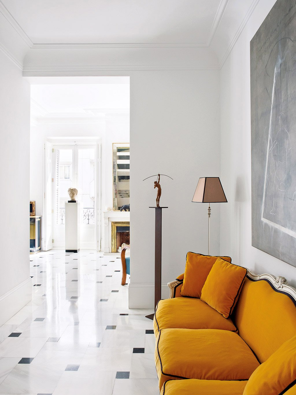 Orange sofa in an entryway with marble floors via @thouswellblog