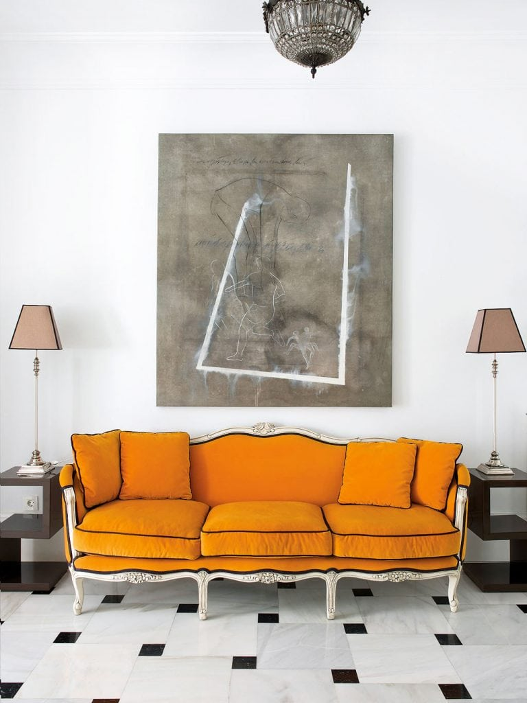 Bold orange sofa upholstery in entryway with marble floor and abstract painting in Spain on Thou Swell #hometour #spanishhome #eclecticstyle #interiordesign #spanishdesign #homedesign #housetour #spanishstyle #homedecorideas