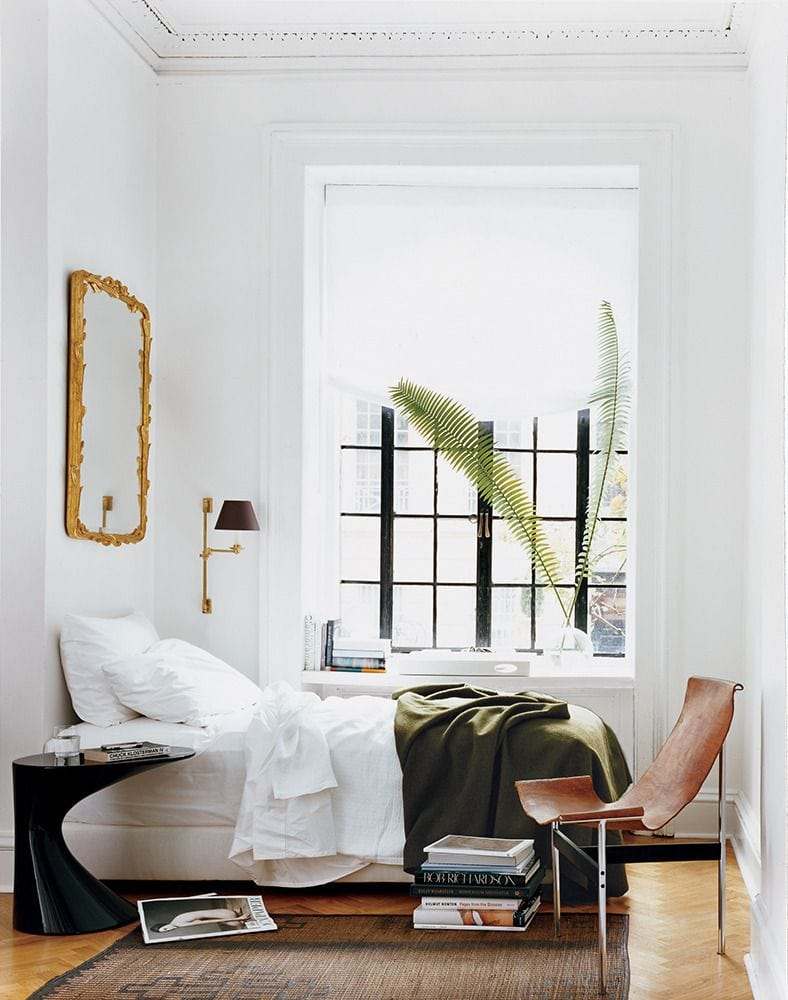Relaxed modern bedroom with gold mirror, sconce, and leather sling chair via @thouswellblog