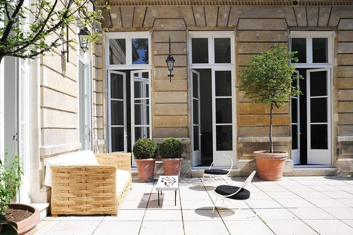French patio with wicker sofa and potted boxwoods via @thouswellblog