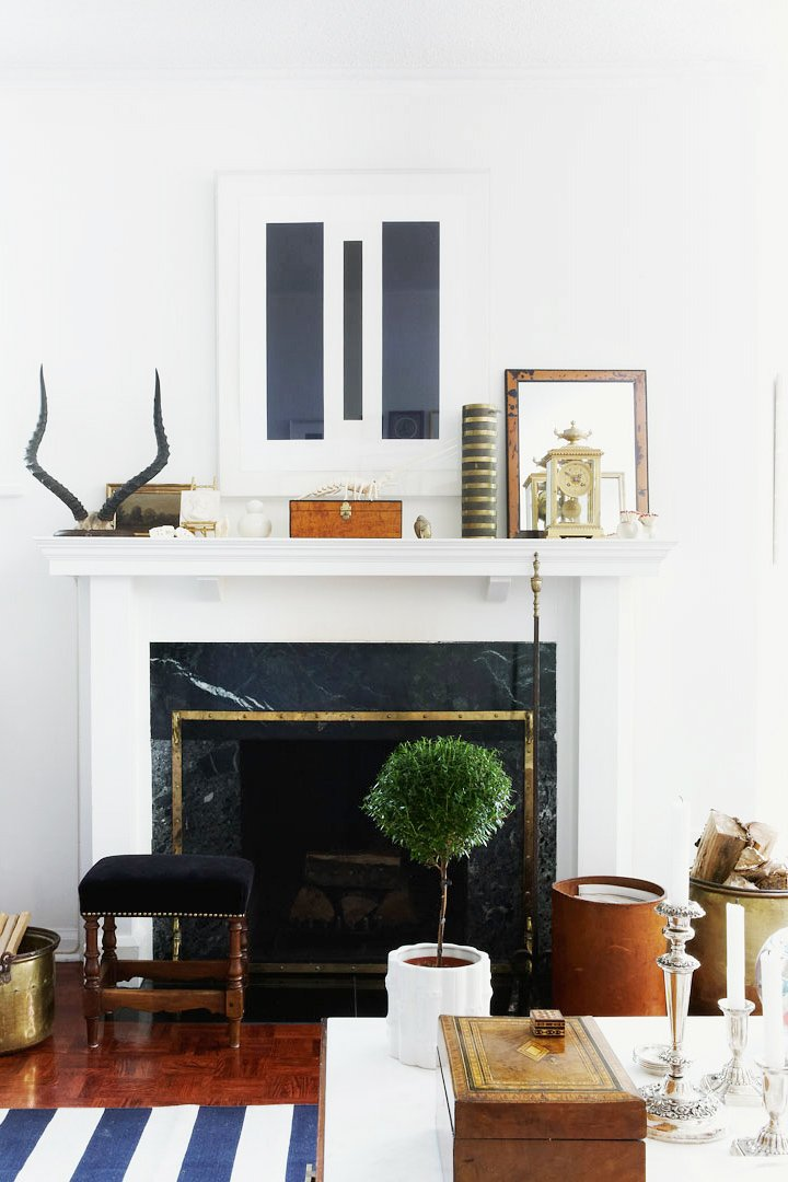 A well-styled fireplace mantel with striped rug and collected objects via @thouswellblog