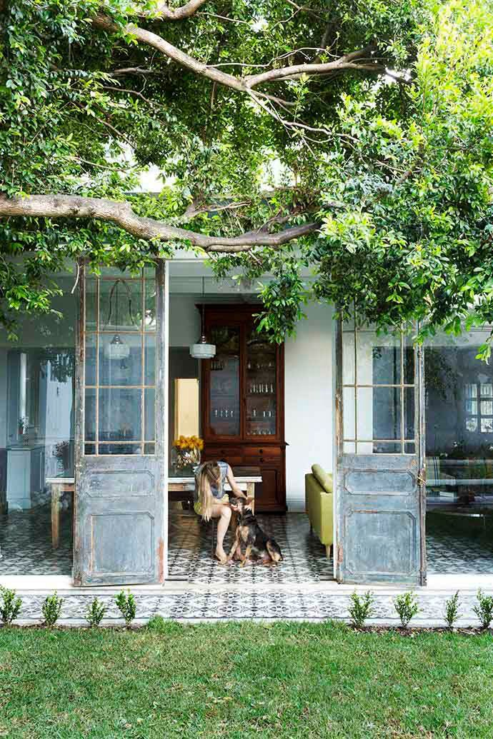 Vintage metal French doors leads to an outdoor tile patio by the dining room via @thouswellblog