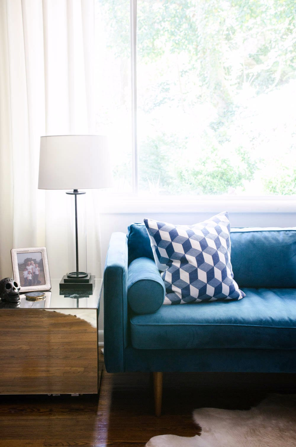 Teal velvet sofa with mirrored side table via @thouswellblog