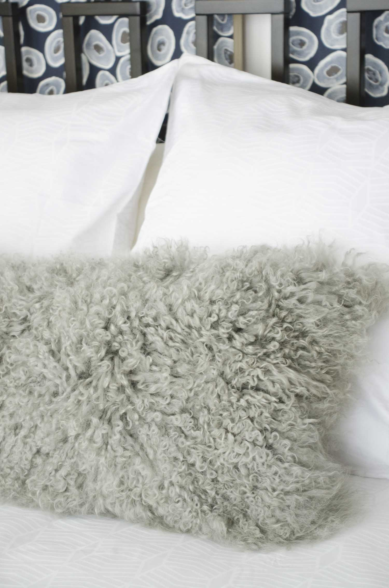 Furry Mongolian lamb lumbar pillow on the bed on @thouswellblog