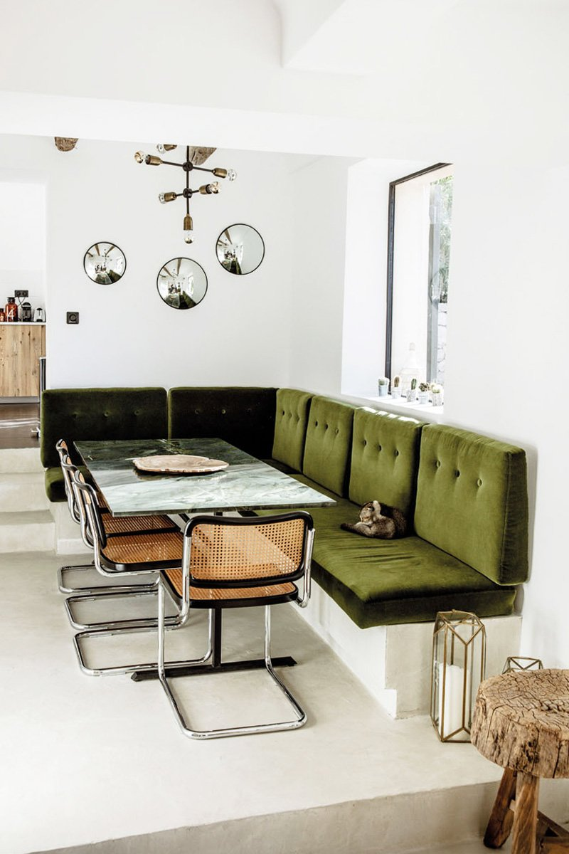 Green velvet dining banquette in a modern dining area via @thouswellblog