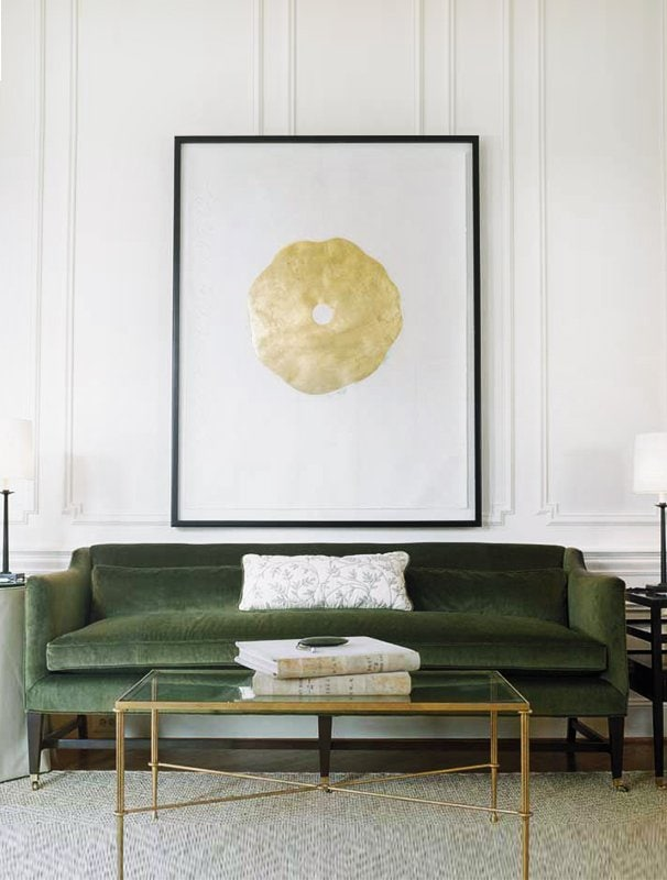 Green velvet sofa with gold coffee table and statement art via @thouswellblog