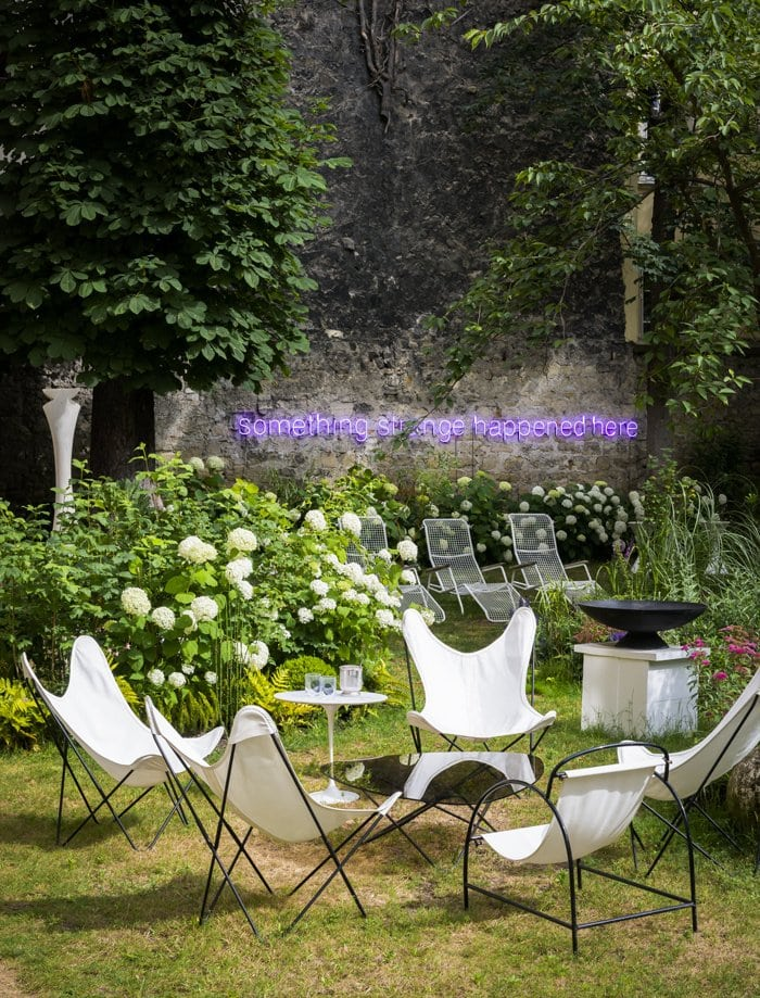 Courtyard garden with white butterfly chairs and neon sign on Thou Swell @thouswellblog