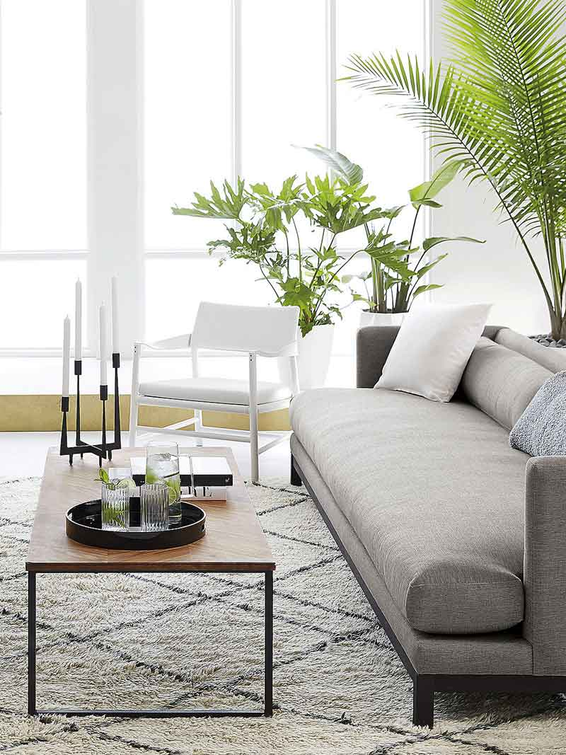 Modern neutral living room with plants and Moroccan style rug on Thou Swell