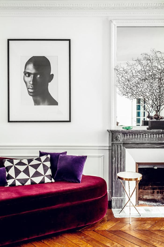 Red velvet sofa in a French living room with black marble fireplace on Thou Swell @thouswellblog