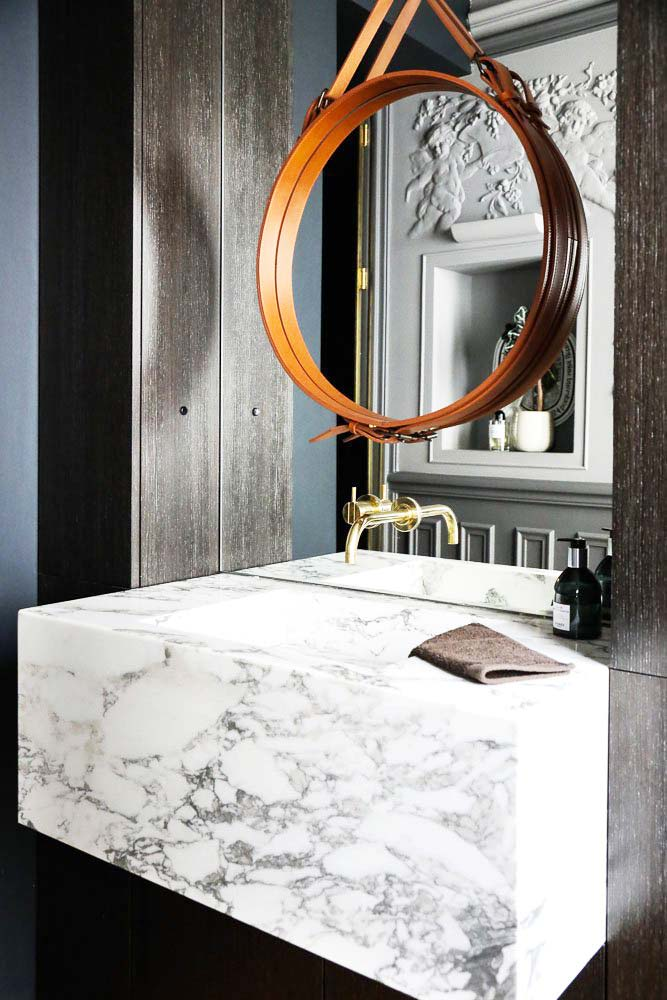 Grey bathroom with round mirror and marble sink on Thou Swell @thouswellblog