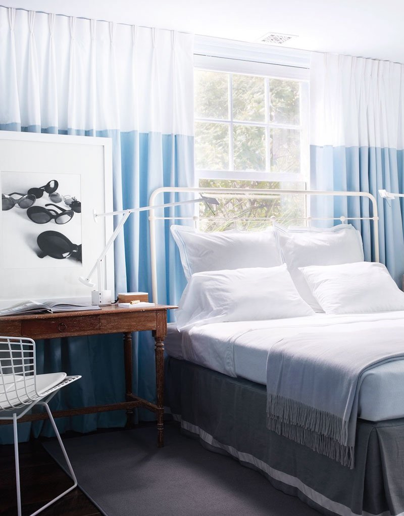 Modern blue bedroom with curtains across the wall and Bertoia desk chair on Thou Swell @thouswellblog