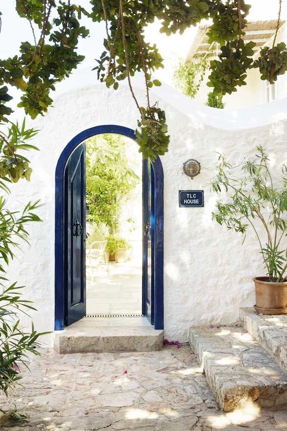 Blue doors in a garden on the coast of Greece on Thou Swell @thouswellblog