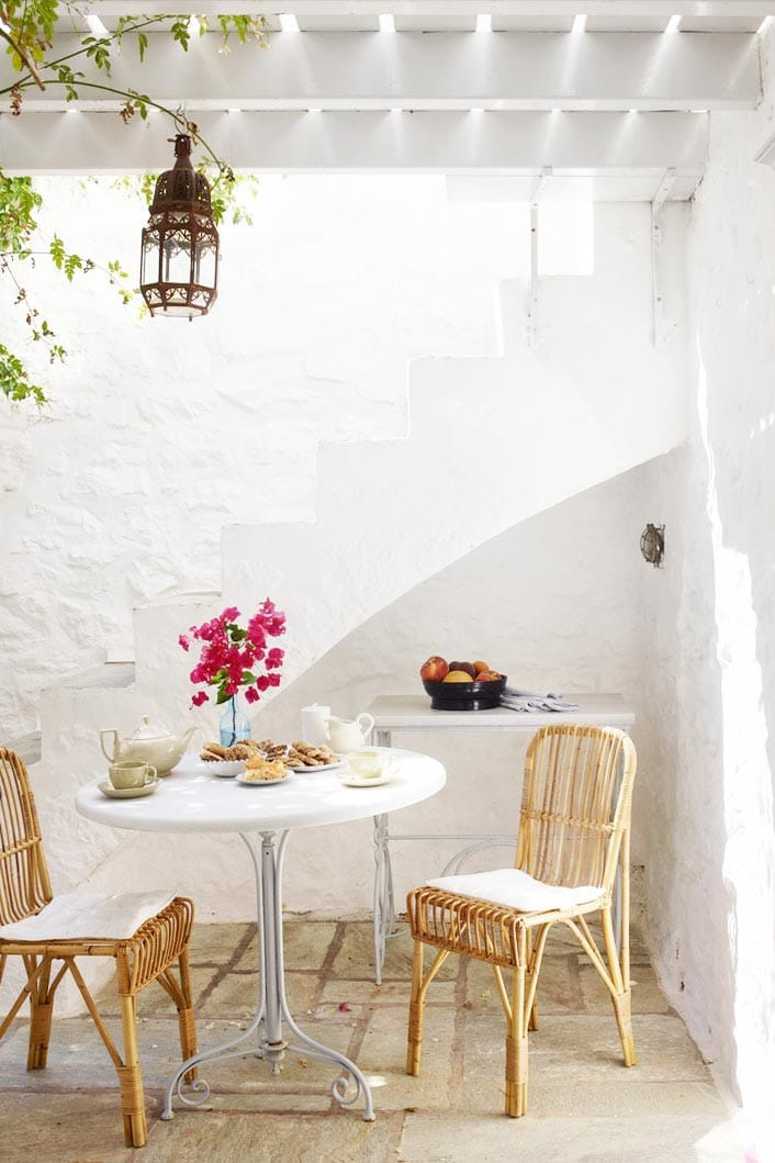 Patio with white walls and rattan dining chairs in Greece on Thou Swell @thouswellblog