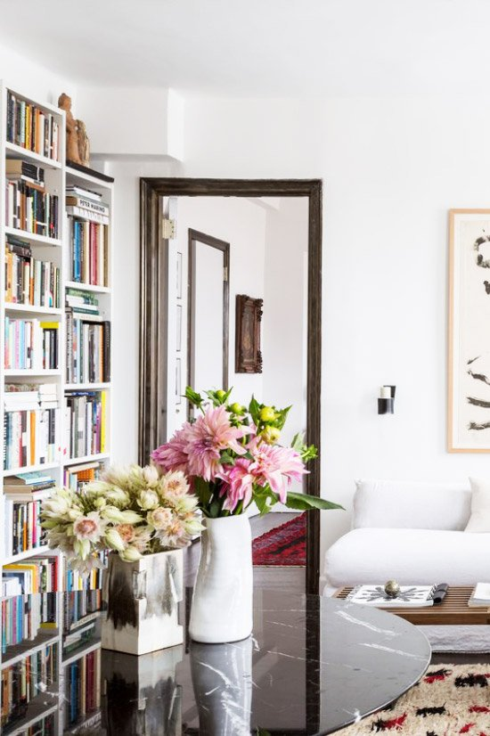 New York City apartment tour bookshelves and flowers on living room table on Thou Swell @thouswellblog