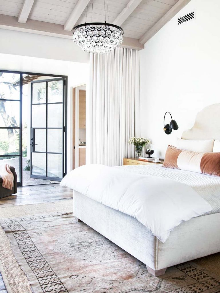 Master bedroom with modern crystal chandelier and black sconces on Thou Swell @thouswellblog