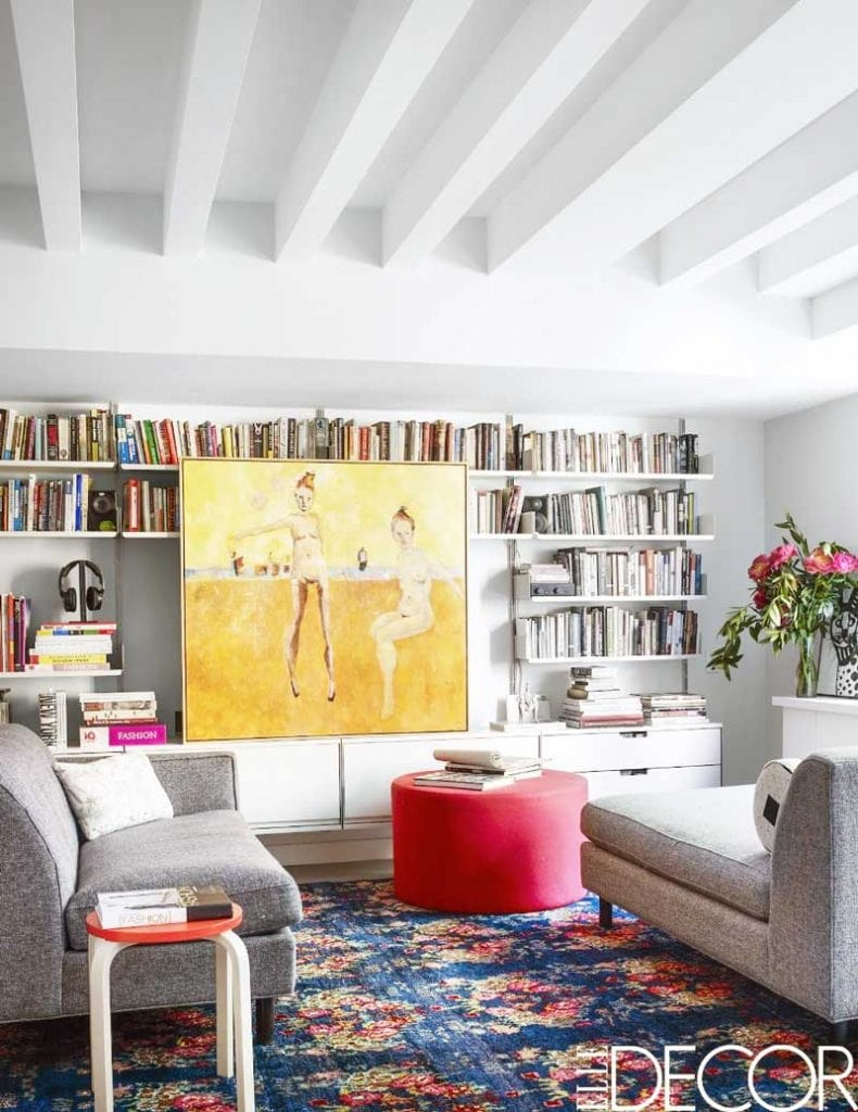 Colorful living room with large yellow painting and red ottoman on Thou Swell @thouswellblog