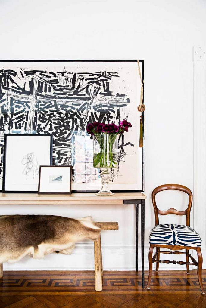 Oversized black and white abstract artwork above console table and hide rug on bench in Manhattan apartment on Thou Swell @thouswellblog