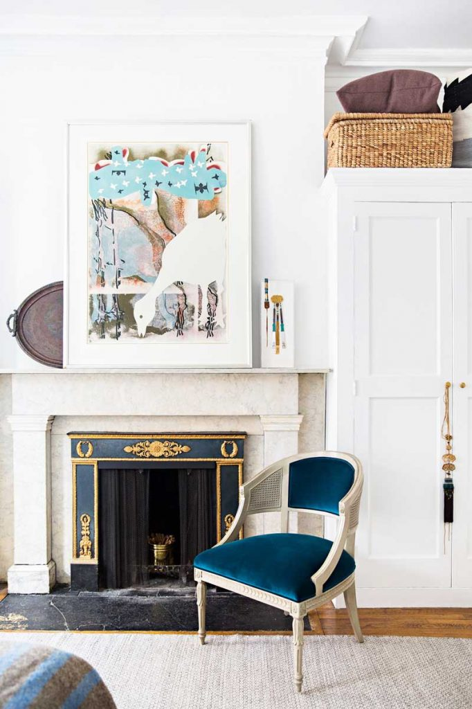 Marble fireplace with blue velvet chair in Manhattan apartment on Thou Swell @thouswellblog