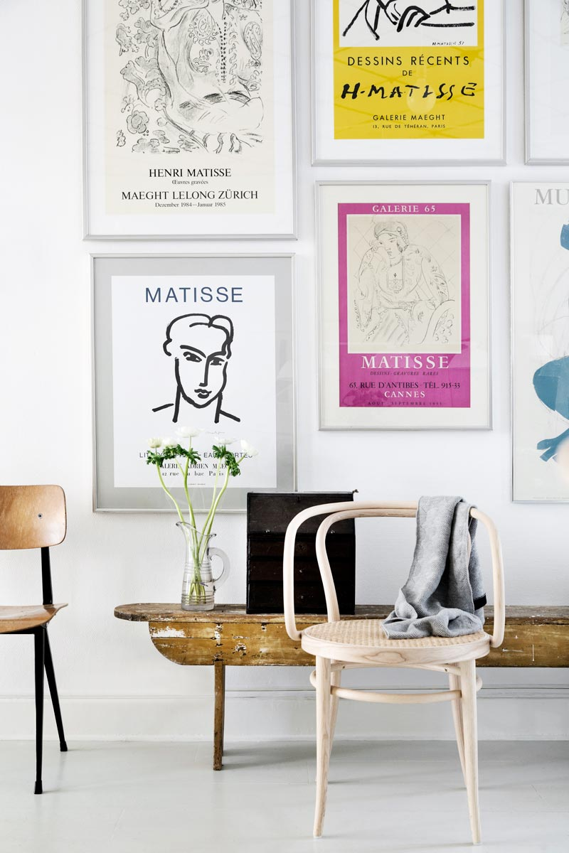 Gallery wall of colorful posters with modern accent chairs on Thou Swell @thouswellblog