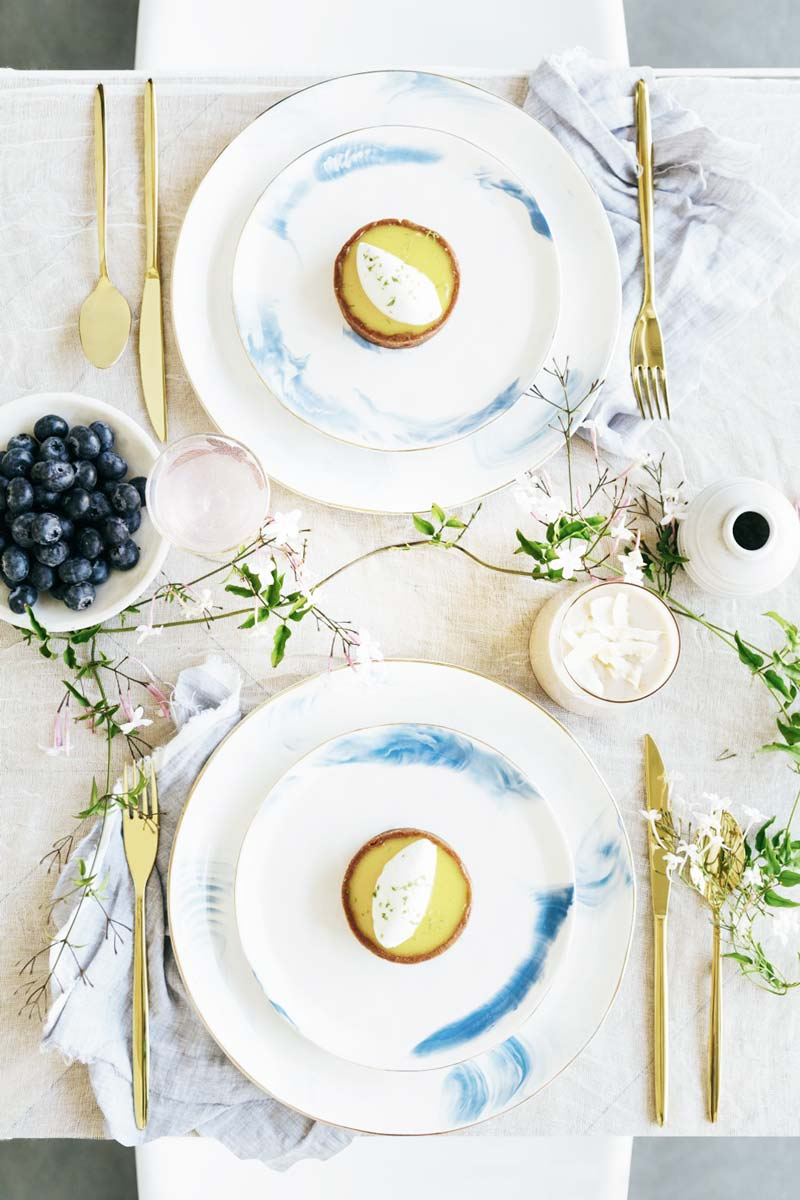 Spring table setting with blue and white plates and greenery runner on Thou Swell @thouswellblog