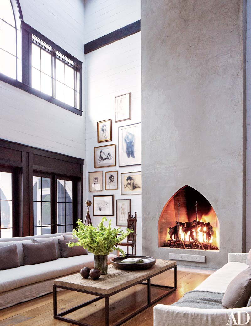 Double-story living room with concrete fireplace chimney and gallery wall on Thou Swell @thouswellblog
