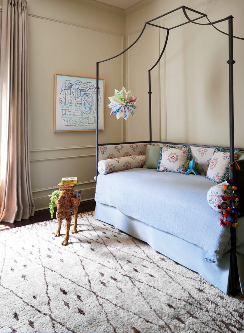 Beige girl's bedroom with metal canopy daybed and Moroccan area rug on Thou Swell @thouswellblog