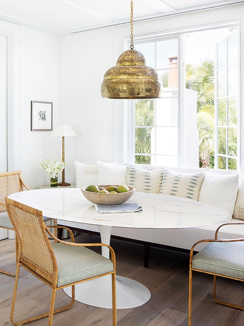 Modern eclectic dining room with brass pendant, banquette seating, and wicker dining chairs on Thou Swell @thouswellblog