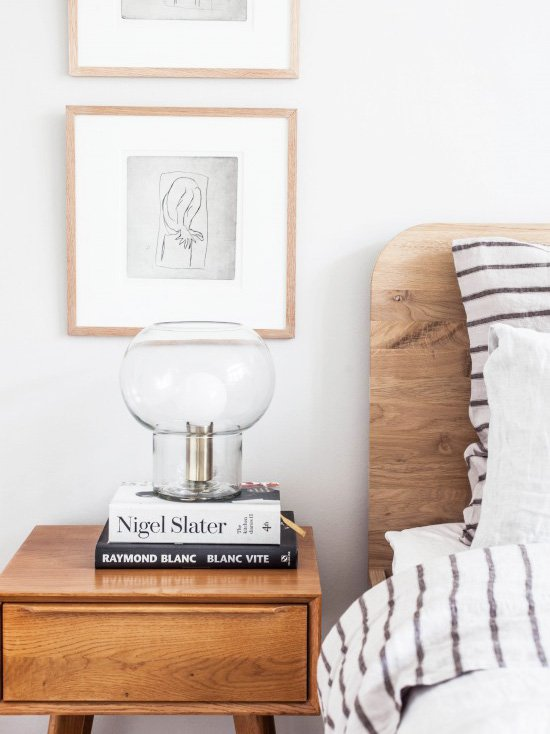 Vintage bedside table and table lamp with art prints and wooden headboard and striped bedding on Thou Swell @thouswellblog