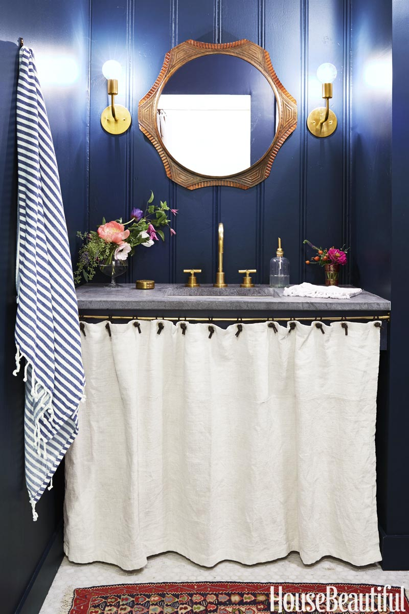Bold blue bathroom in Farrow & Ball Hague Blue with brass mirror and modern sconces on Thou Swell @thouswellblog