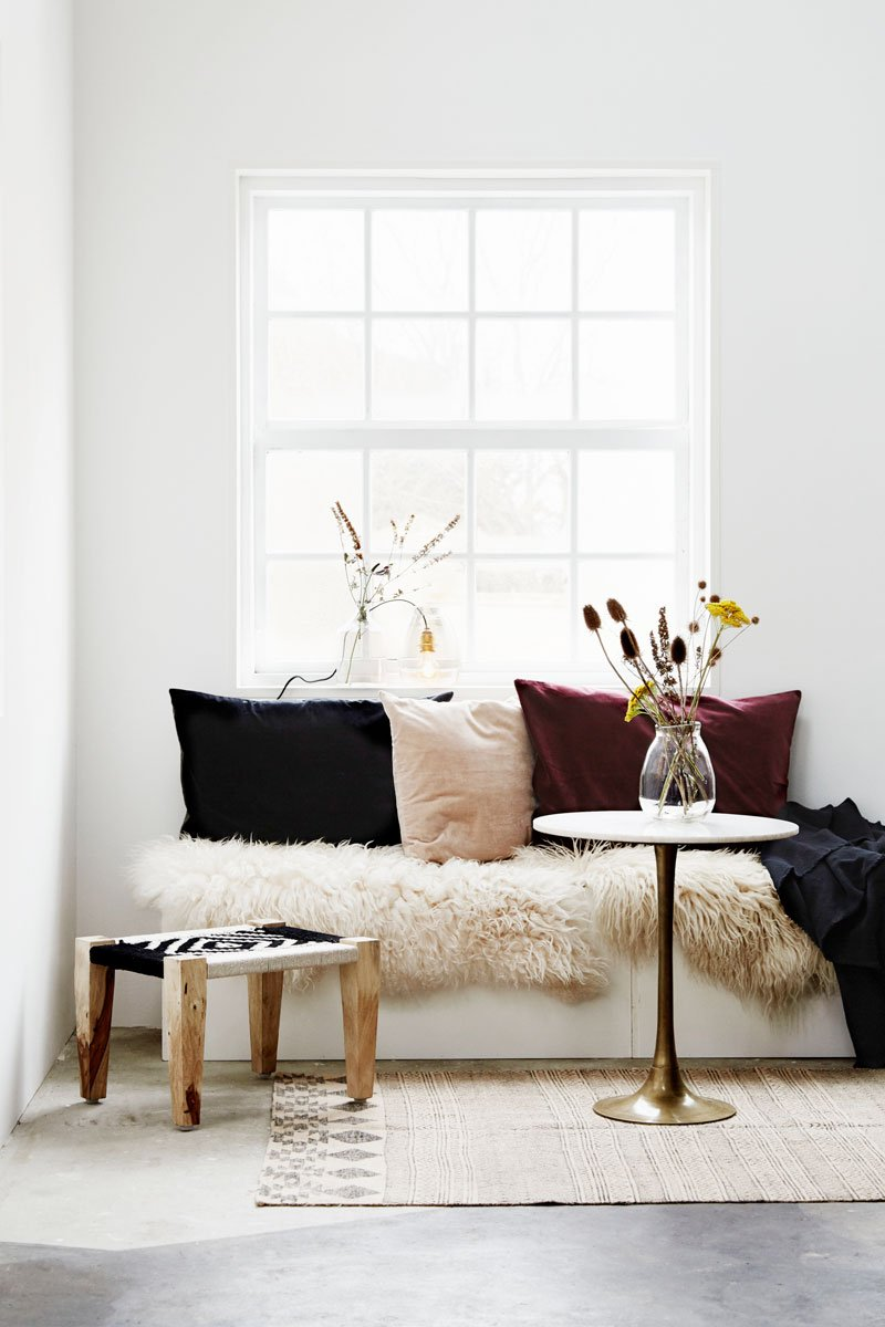 Window seat with velvet throw pillows, sheepskin and woven stool on Thou Swell @thouswellblog