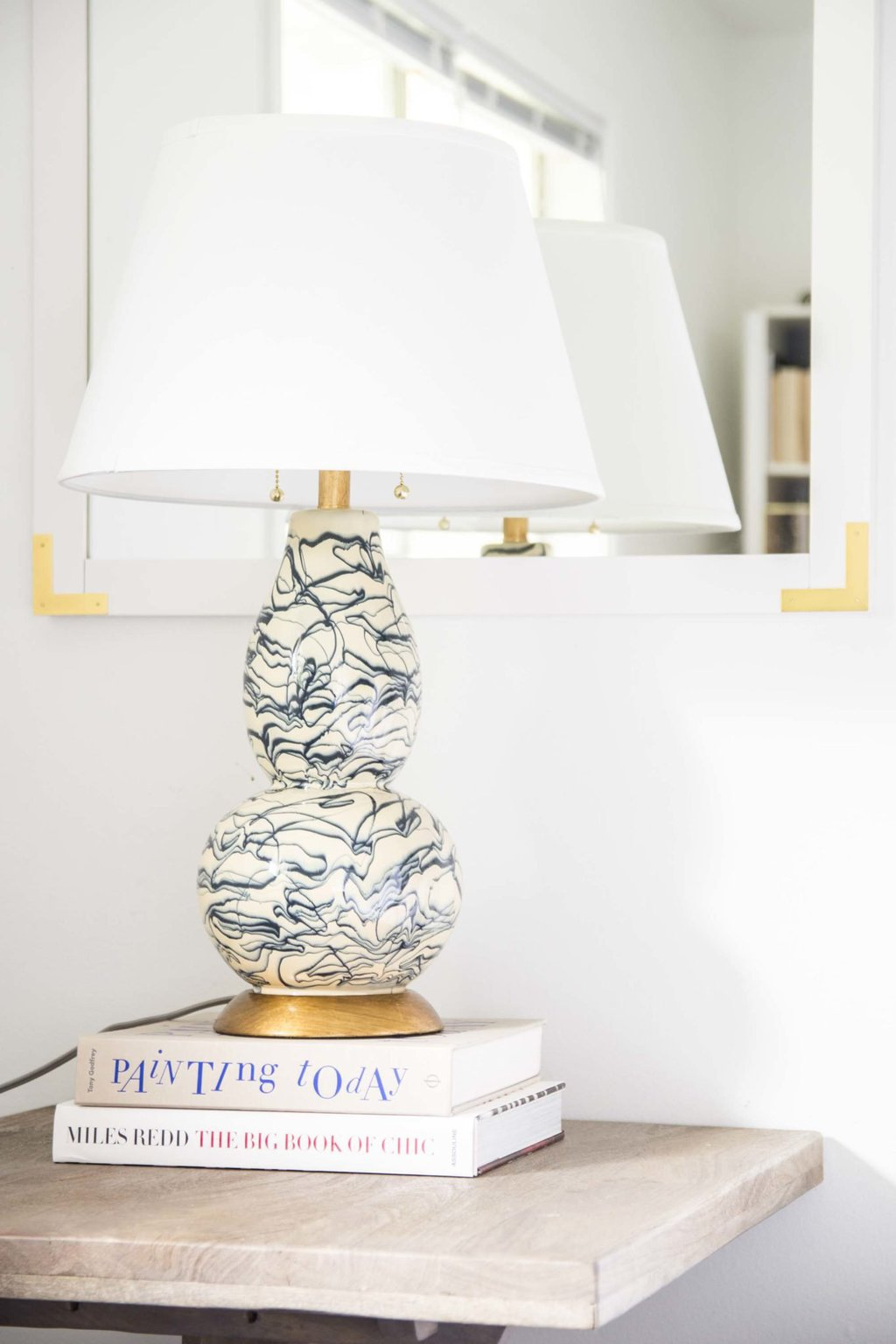 Blue and white swirl lamp with white and gold mirror above nightstand on Thou Swell @thouswellblog
