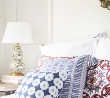 Colorful patterned throw pillows on the bed in a simple white bedroom on Thou Swell @thouswellblog