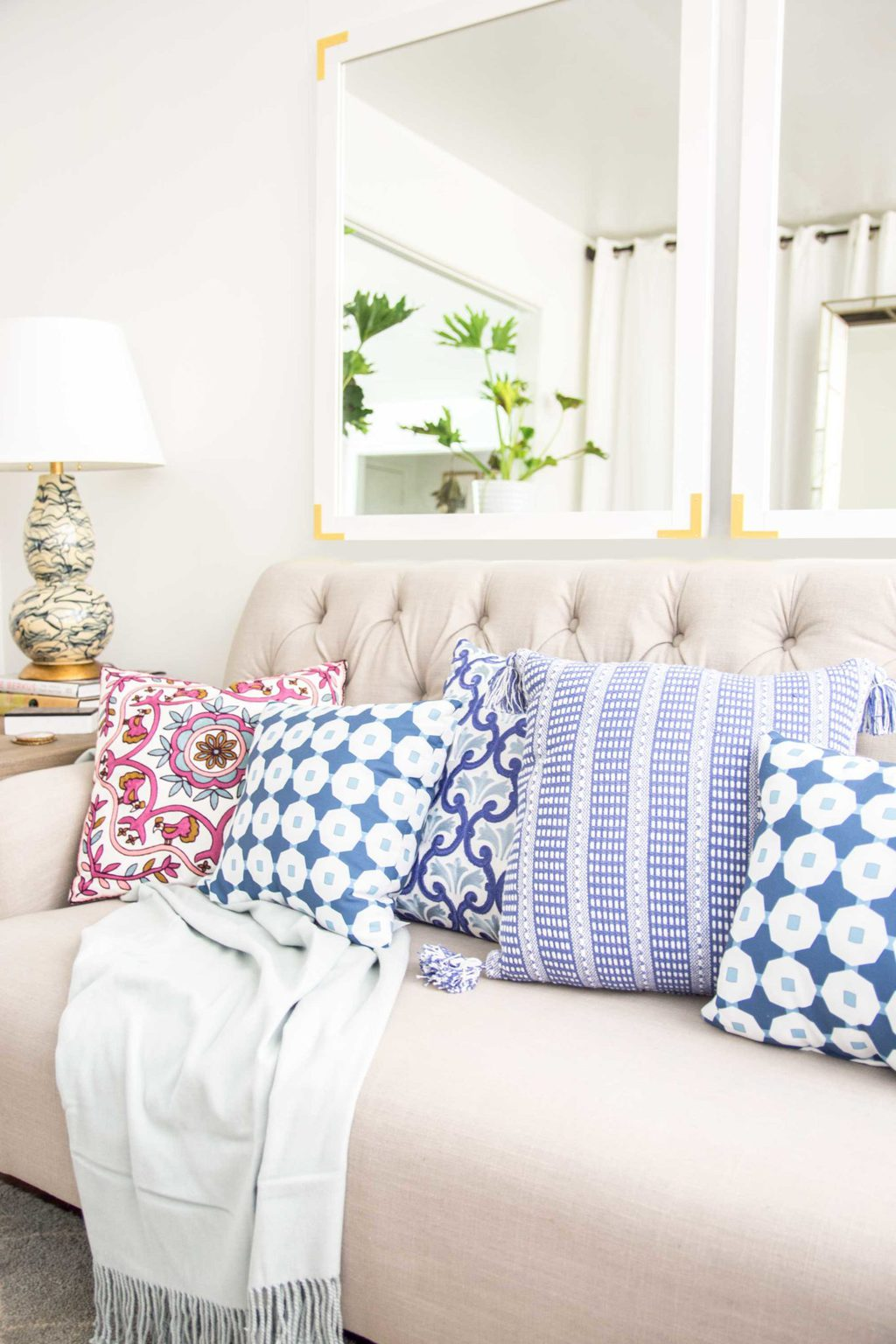 Colorful patterned throw pillows on a tufted sofa in the living room on Thou Swell @thouswellblog