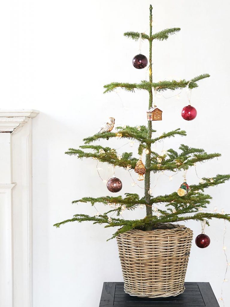 Christmas tree in basket with unique ornaments on Thou Swell @thouswellblog