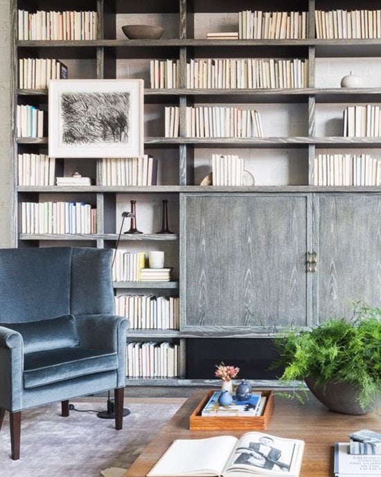 Washington D.C. loft with floor-to-ceiling bookcase and velvet wingback chair on Thou Swell #bookcase #bookshelves #books #bookshelfwall #greywood #grey #design #homedesign #interiordesign